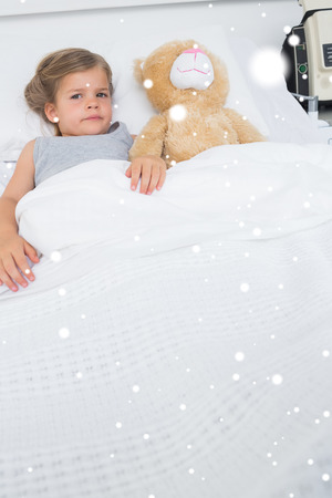 Girl with teddy bear lying in hospital bed against snow falling