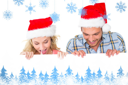 Festive couple smiling from behind poster against snowflakes and fir trees