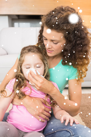Caring mother helping her little daughter blow her nose against snow falling