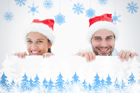 Festive young couple smiling at camera against snowflakes and fir trees