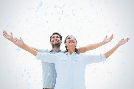 Cute couple standing with arms out against snow falling