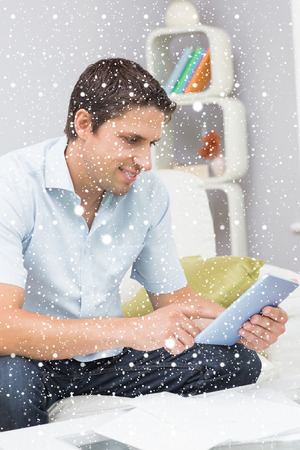 Smiling man with bills using digital tablet in the living room against snow falling