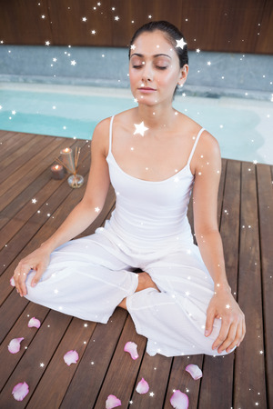 Peaceful brunette in white sitting in lotus pose surrounded by petals against night sky