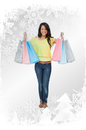Beaming woman student with shopping bags against christmas frame