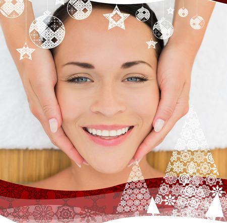Peaceful brunette enjoying a facial massage against christmas themed frame