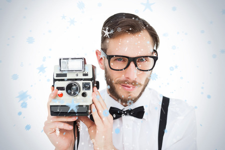 Geeky hipster holding a retro camera against snow falling