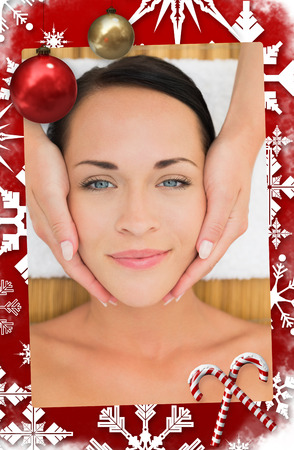 Peaceful brunette enjoying a facial massage against christmas themed page