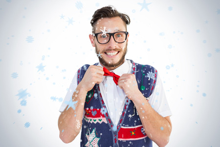 Geeky hipster wearing christmas vest against snow falling