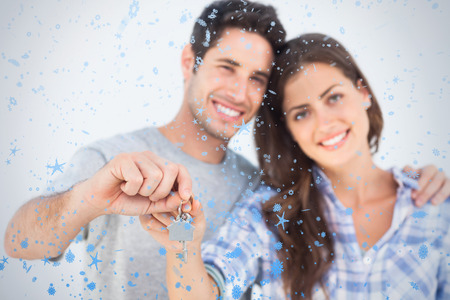 Man and wife holding a key with a house keychain against snow falling