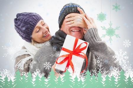Happy mature woman hiding gift from partner against snowflakes and fir trees in green
