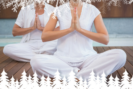 Couple in white sitting in lotus pose with hands together against fir tree forest and snowflakes