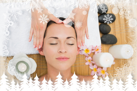 Smiling brunette enjoying a head massage against fir tree forest and snowflakes