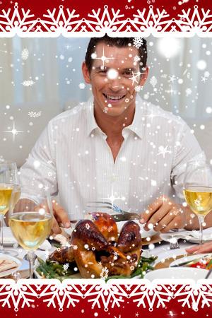Smiling man eating turkey in Christmas dinner against snow falling