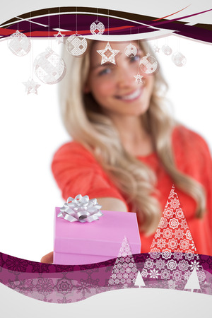 Young woman giving a gift against christmas frame