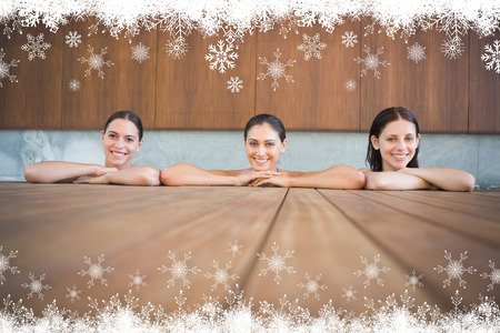 Cheerful young women in swimming pool against fir tree forest and snowflakes