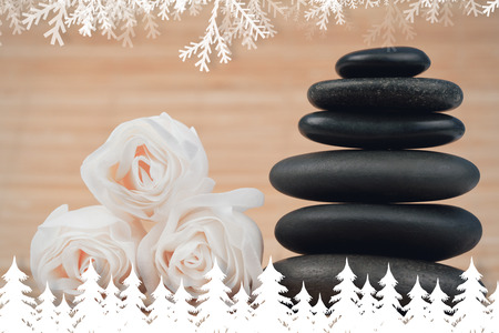 Fir tree forest and snowflakes against close up roses and a black pebbles stack