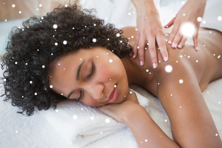 Gorgeous woman enjoying a shoulder massage against snow