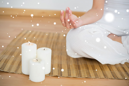 Photo for Woman sitting in lotus pose beside white candles against snow - Royalty Free Image