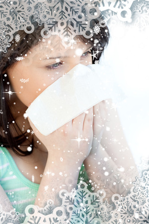 Portrait of a sick brunette teen girl blowing against snow falling
