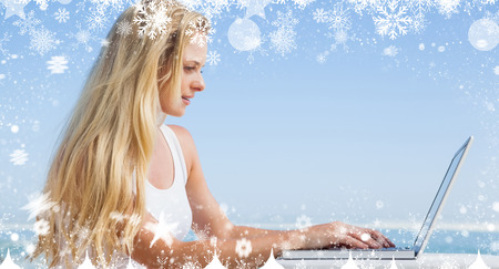 Composite image of a Pretty blonde using her laptop at the beach against snow