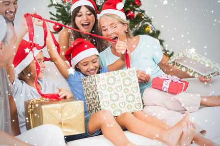 Composite image of Happy family at christmas opening gifts together against snow