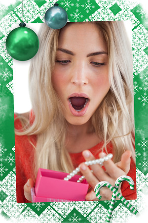 Shocked woman discovering necklace in a gift box against christmas frame
