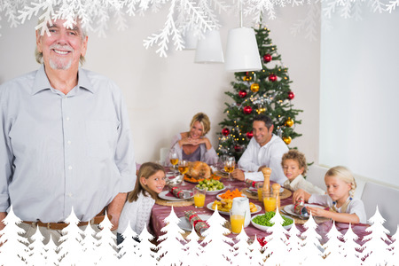 Smiling grandfather standing at the dinner table against fir tree forest and snowflakes