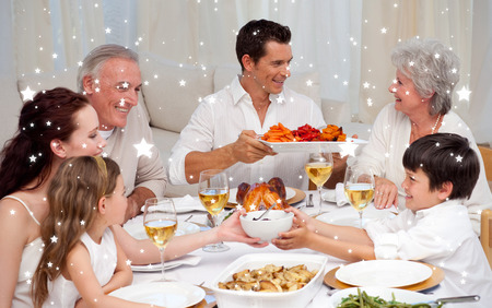 Composite image of Family having a big dinner at home against snow