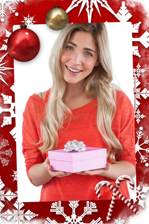 Blonde woman receiving a gift against christmas themed page
