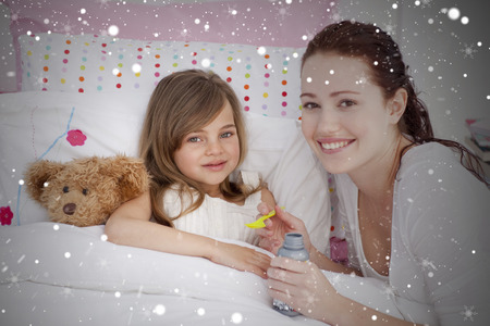 Composite image of sick little girl in bed taking cough medicine against snow