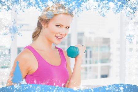 Pretty blonde lifting dumbbells and smiling at camera against snow