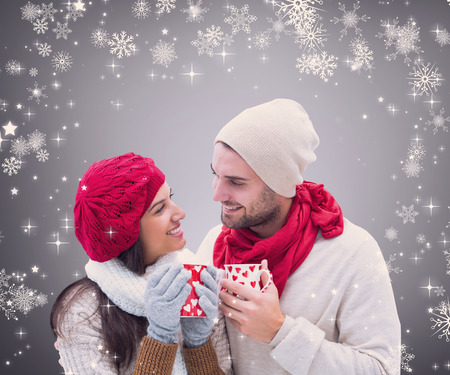 Composite image of winter couple holding mugs against grey vignette