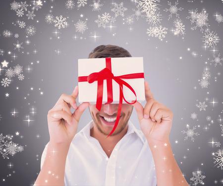 Man holding gift against grey vignette