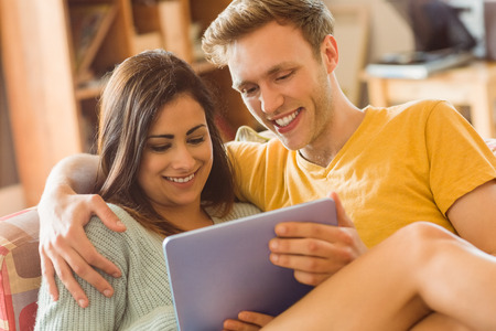 Young couple cuddling on the couch with tablet pc at home in the living room