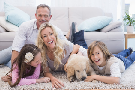 Foto de Laughting family with their pet yellow labrador on the rug at home in the living room - Imagen libre de derechos