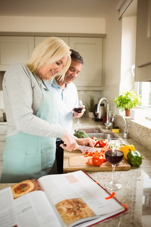 Mature couple preparing vegetables together at home in the kitchen