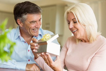 Happy mature man offering wife a gift at home in the kitchen