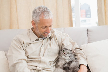 Happy man with his pet cat on sofa at home in the living room
