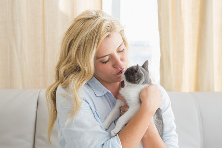 Pretty blonde with pet kitten on sofa at home in the living room