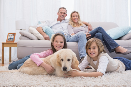 Foto de Cute siblings playing with dog with their parent on the sofa at home in the living room - Imagen libre de derechos