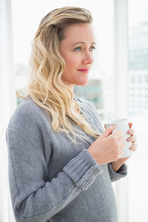 Smiling blonde woman holding mug of coffee looking away at home in the living room