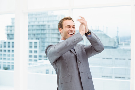 Cheerful young businessman clapping hands in office