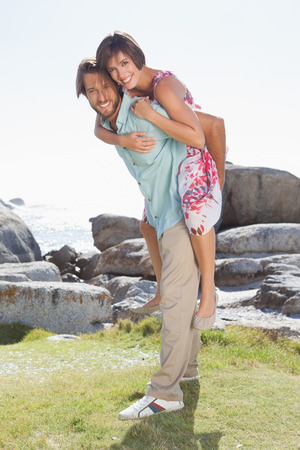Gorgeous couple having fun by the coast on a sunny day