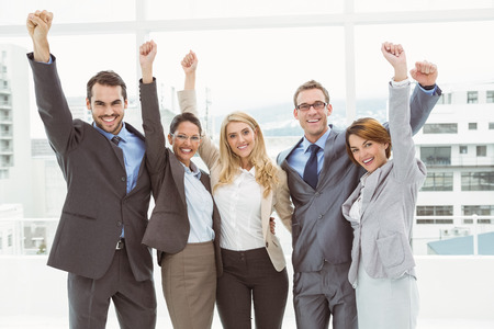Photo pour Portrait of cheerful business people cheering in the office - image libre de droit