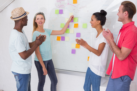 Creative business team clapping hands by sticky notes on wall