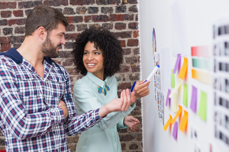Photo for Creative business team looking at sticky notes on wall - Royalty Free Image