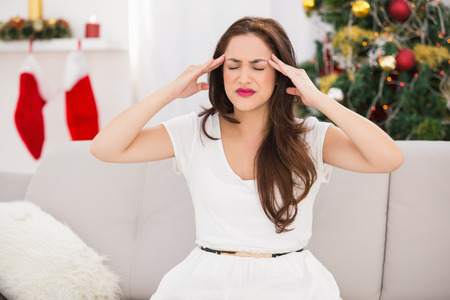 Brunette getting a headache on christmas day at home in the living room