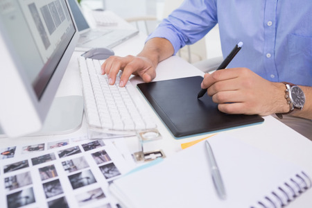 Graphic designer using digitizer at his desk in creative office