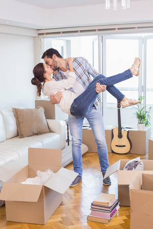 Cute couple unpacking cardboard boxes in their new home