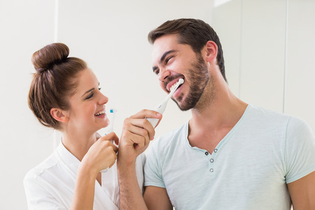 Photo pour Young couple brushing their teeth at home in the bathroom - image libre de droit